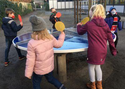 Kinder, die an einer runden Tischtennisplatte spielen