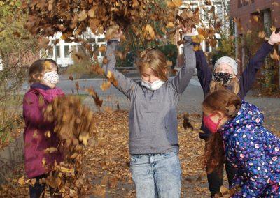 Kinder werfen Laub