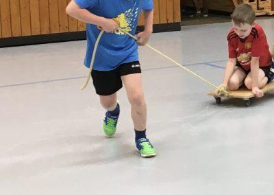 Kinder spielen in der Turnhalle mit Rollbrettern